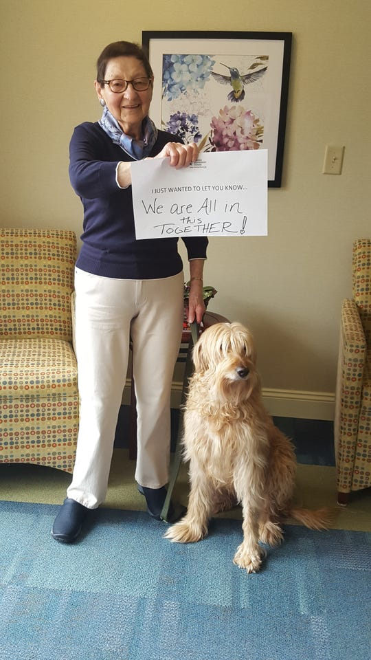 """United Methodist Homes Hilltop Campus resident Magdelena (Lanie) Nilsen with dog Lola holds a sign that reads """"I just wanted to let you know we are all in this together."""""""