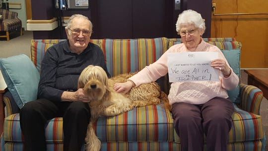"""United Methodist Homes Hilltop Campus residents David Edwards and Helen Tellep hold a sign that reads, """"I just wanted to let you know we are all in this together."""""""