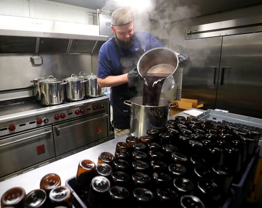 Nathan Sylling is enveloped in steam as he pours a pot of elderberry juice into another pot while making batches of his Sylling's elderberry syrup in the commercial kitchen of the Elks Lodge in Gig Harbor on Thursday.