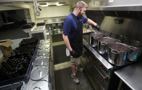 Nathan Sylling stirs pots of boiling elderberries as he makes batches of his Sylling's elderberry syrup in the commercial kitchen of the Elks Lodge in Gig Harbor on Thursday.