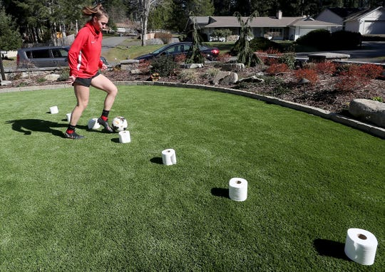 North Mason' soccer player Sophia Green uses toilet paper roles as makeshift cones in the front yard of her Allyn home on Thursday, March 19, 2020.