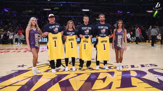 Olympic surfers Caroline Marks and Kolohe Andino, along with USA Surfing CEO Greg Cruse and Team USA junior national coach Brett Simpson, receive special Los Angeles Lakers jerseys during an NBA game this season at Staples Center.