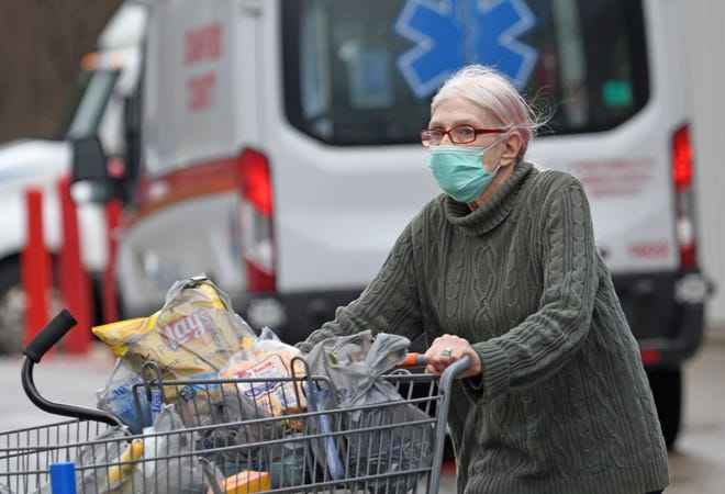 A woman wearing a surgical mask pushes her groceries from the Walmart store in Bucyrus on a recent morning.