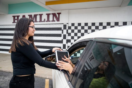 Rebecca Lopez delivers a to-go order to a customer waiting in a vehicle at Hamlin Fountain & Gifts + Bakery on Friday, March 20, 2020. Beginning Saturday, orders can be placed via phone and employees will deliver it to vehicles or customers can pick it up at the front register. The soda fountain has been in business since 1960.