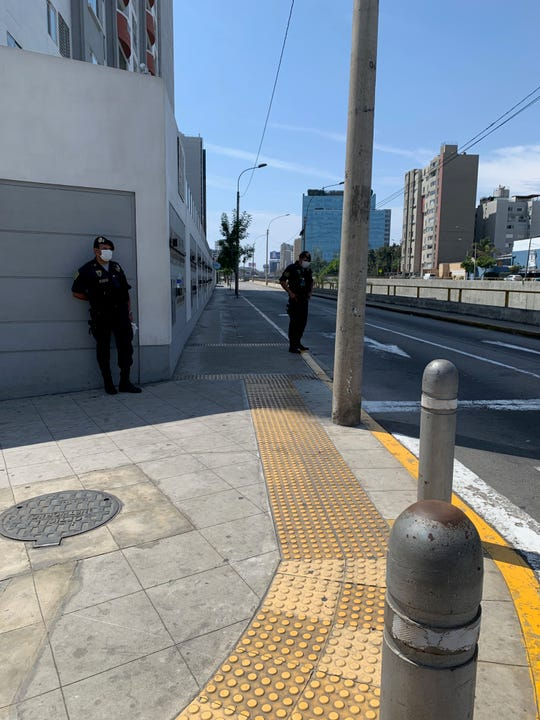 Streets in Lima, Peru are abandoned, save for military officers in masks enforcing the country's shelter-in-place orders from Peru's president to combat COVID-19 coronavirus' spread.