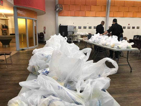 Staff at Cathedral Kitchen in Camden assemble take-away bags of food for homeless people. The kitchen has suspended its in-house meals during the COVID-19 outbreak.