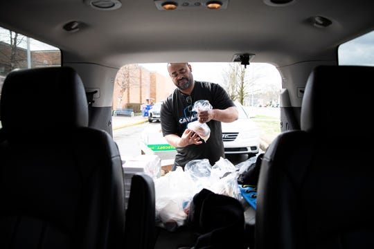 Geoffrey Duncan prepares bags of food to be delivered to Integrated Service clients on March 20, 2020.