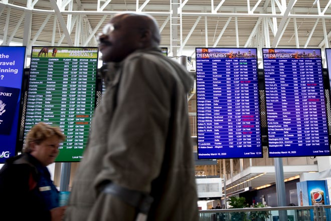 A traveler walks past the departure and arrival boards at Cincinnati/Northern Kentucky International Airport on Wednesday, March 18, 2020, in Hebron, Ky.