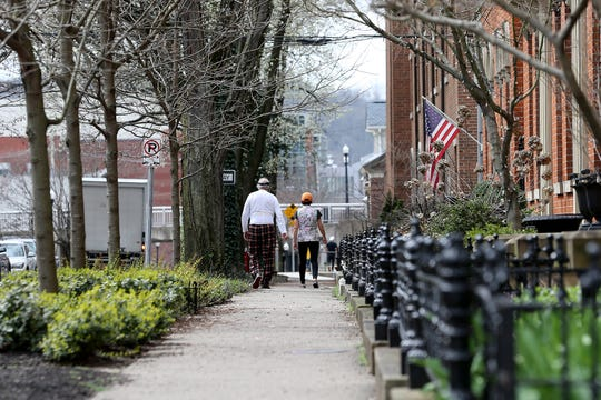 A man and woman along East Third Street, Friday, March 20, 2020, in Newport, Ky.
