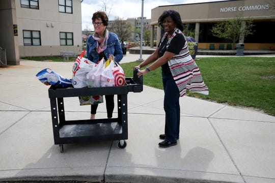 Debbie Buckley, the city of Fort Thomas' economic development director, left, drops off food to Rochelle Shields, Northern Kentucky University's associate director of operations for housing, right, for Northern Kentucky University students who remain on campus during the new coronavirus pandemic, Friday, March 20, 2020.