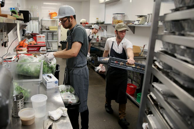 Mita's pastry chef Brian Neumann, left, prepares salads as sous chef Nick Hartshorn works to prepare meals for out-of-work workers from the restaurant and hospitality industries affected by the coronavirus pandemic, Thursday, March 19, 2020, at Mita's restaurant and bar. The restaurant has opened its doors every day between 5 and 8:30 p.m. for laid off restaurant and hospitality workers to offer meals, toiletries, diapers and canned good for the next to weeks. Workers must show identification and a paystub to prove they work in the restaurant or hospitality industries.
