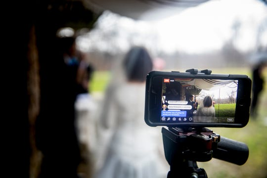 A livestream video of Chana Wolfson and Scott Smith's wedding is watched by friends and family around the country on Thursday, March 19, 2020 at French Park in Amberley Village. The couple was supposed to get married at the end of the month, but moved their wedding up due to the new coronavirus pandemic and concerns of travel restrictions.