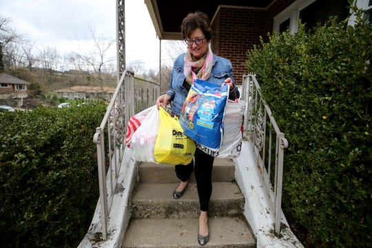 Debbie Buckley, the city of Fort Thomas' economic development director, collects food to drop off to Northern Kentucky University students, who remain on campus during the new coronavirus pandemic, Friday, March 20, 2020.