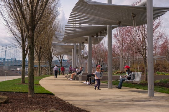 Visitors of Smale Riverfront Park in Cincinnati swing on Friday, March 20, 2020.