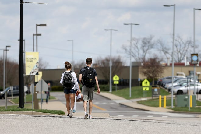 Northern Kentucky University students walk after picking up donated food, Friday, March 20, 2020, at Northern Kentucky University in Highland Heights, Ky.