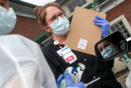 Reflected in her car's side mirror, Cynthia Barnes, a Clarksville resident, answers questions pertaining to her symptoms before taking the swab test for COVID-19 coronavirus at the Montgomery County Health Department in Clarksville, Tenn., on Friday, March 20, 2020.