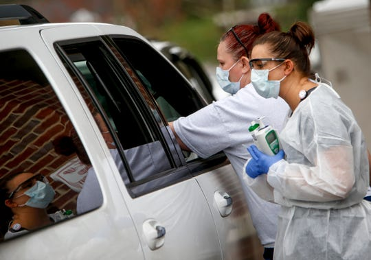Montgomery County medical staff speak with patients through their car windows asking about symptoms before carrying out the COVID19 coronavirus test at the Montgomery County Health Department in Clarksville, Tenn., on Friday, March 20, 2020.