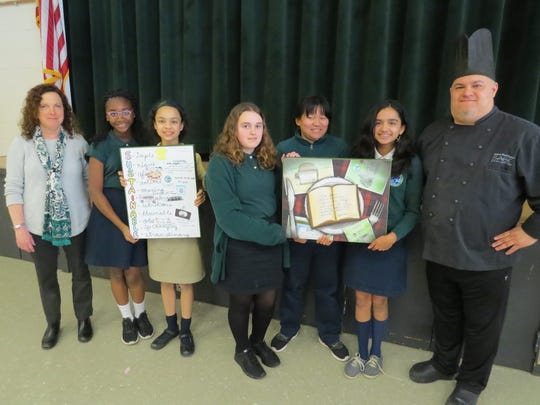 The students proudly display their posters with Chef Anibal Rodriguez.