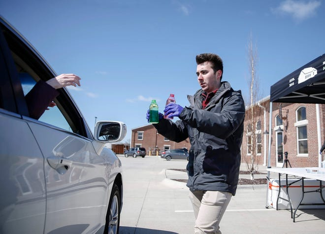 A volunteer hands out hand sanitizer to a member of the community at The Foundry in West Des Moines on Friday, March 19, 2020.