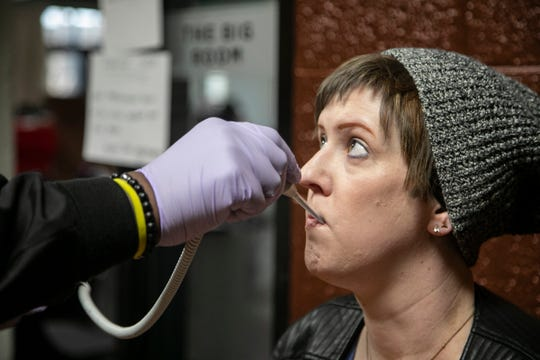 Red Cross mobile unit assistant Kevin Sirmans takes the temperature of Sarah Previch, 37, of Ferndale who signed up to donate blood Thursday, March, 19, 2020 at the Pleasant Ridge Community Center in Pleasant Ridge