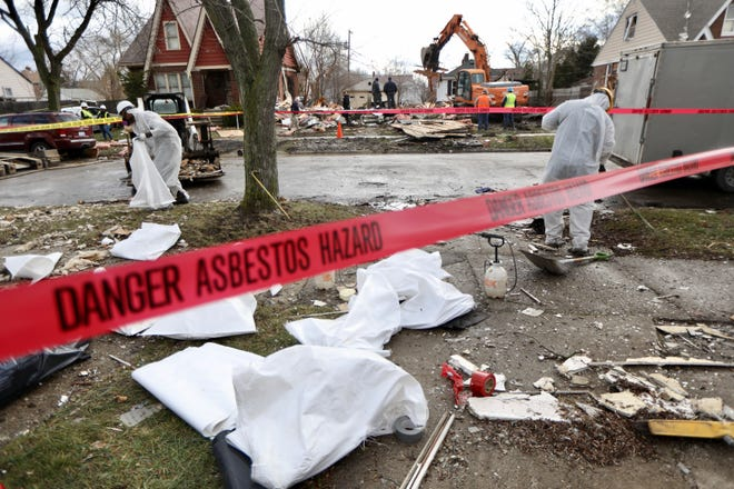 A crew cleans up asbestos debris in the yard across the street from a home on Archdale street near Warren Avenue in Detroit that exploded around 4 a.m. on Friday, March 20, 2020.
