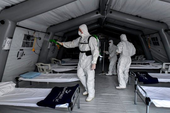 Staffers sanitize the Samaritan's Purse field hospital that is being set up in Cremona, northern Italy, Friday, March 20, 2020. A Christian evangelical group headed by the son of the late televangelist Billy Graham has sent a field hospital to northern Italy to tend to coronavirus patients, joining China in offering aid to Italy's overwhelmed health care system.