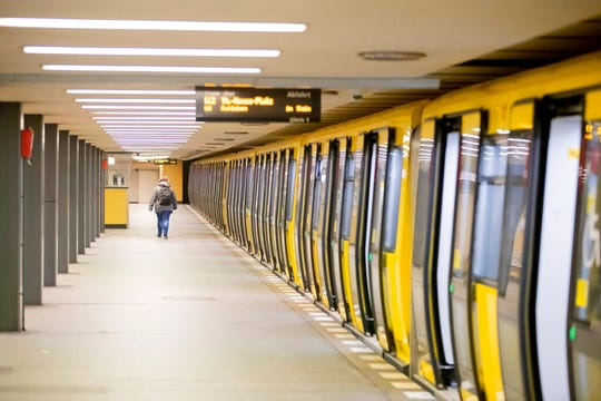 A woman walks on a deserted platform of the underground station Zoologischer Garten in Berlin Friday morning, March 20, 2020. In order to slow down the spread of the novel coronavirus, the federal government has considerably restricted public life.