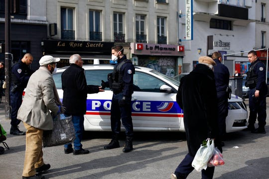 Police officers check people at the entrance of the open air market of Belleville, in Paris, Friday, March 20, 2020. French President Emmanuel Macron said that for 15 days starting at noon on Tuesday, people will be allowed to leave the place they live only for necessary activities such as shopping for food, going to work or taking a walk.