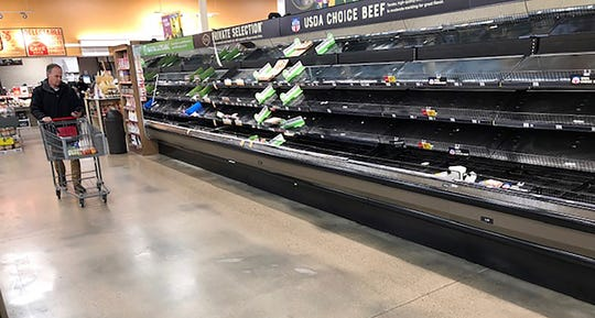 A lone shopper pushes his cart past the empty meat display in a King Soopers grocery store in Denver on March 14, 2020.