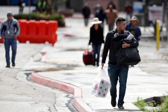 A man carries toilet paper after crossing the border from Tijuana, Mexico, to San Diego, Wednesday, March 18, 2020, in San Diego.