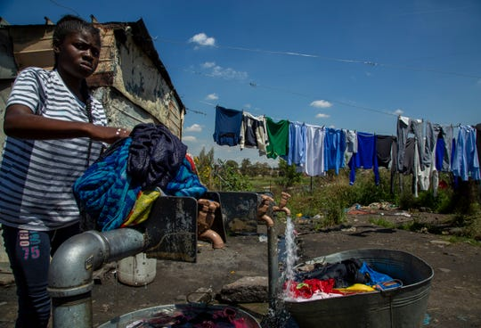 A woman washes her laundry next to a communal taps at Nomzamo squatter camp in Soweto, South Africa, Thursday, March 19, 2020.