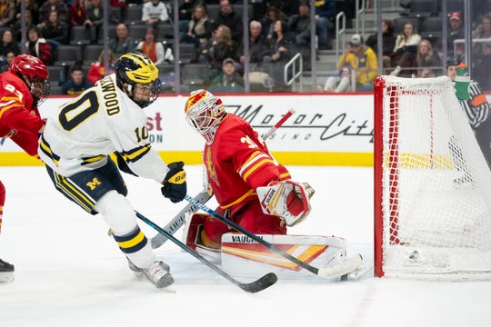 Michigan forward Will Lockwood, left, scores a goal against Ferris State goaltender Austin Shaw at the 2019 Great Lakes Invitational at Little Caesars Arena.
