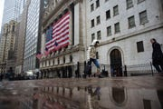 A pedestrian wearing a surgical mask and gloves walks past the New York Stock Exchange on Thursday in New York.