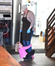 Wren Peck, 6, plays with her mother Kristen Calverley in between working on orders at Michigan & Trumbull pizza in Detroit and watching her 2 children, who are not at school due to coronavirus restrictions.