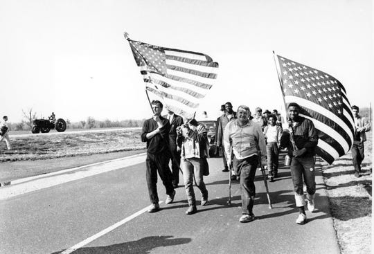 Civil rights marchers carry flags and play the flute as they approach their goal from Selma to Montgomery, Alabama's state Capitol on March 24, 1965.