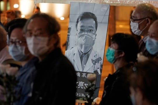 FILE - In this Feb. 7, 2020, file photo, people wearing masks attend a vigil for Chinese doctor Li Wenliang, who was reprimanded for warning about the outbreak of the new coronavirus, in Hong Kong.