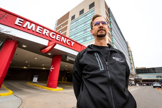 Dr. Chris Port, M.D. stands outside the emergency room at Spectrum Health in Grand Rapids Friday, March 20, 2020.