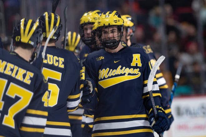 Michigan forward Will Lockwood, right, celebrates a goal against Michigan Tech at the 2018 Great Lakes Invitational at Little Caesars Arena.