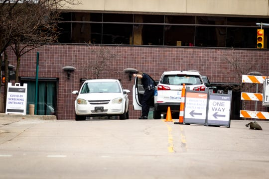 Security personnel check potential patients for COVID-19 symptoms outside the emergency department at Spectrum Health Hospital in Grand Rapids on Friday, March 20, 2020.