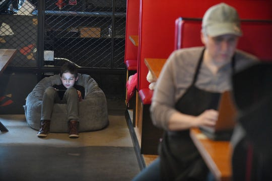 Oliver Peck, 11 plays a game on his tablet as his mother Kristen Calverley works on filling out forms for SBA disasters assistance loans for small businesses in between working on orders at Michigan & Trumbull pizza in Detroit.