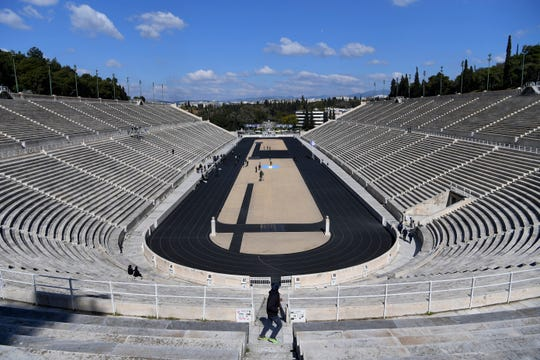 Empty tribunes are seen during the Olympic flame handover ceremony Thursday.