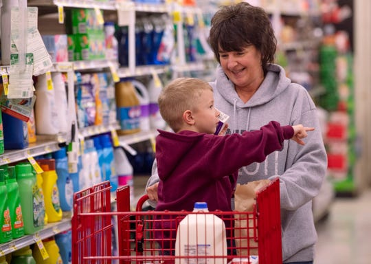 Zane Crotty, 5, and his grandmother, Sheila Duncan, of Mount Vernon, Ind., shop at the McKim's IGA in Mount Vernon, Ind., Friday morning, March 20, 2020. The youngster was proudly displaying his bag lunch the ladies at the deli counter gave him. He was especially excited about the apple in the bag. The store has been offering free bag lunches for kids who have been missing school due to the coronavirus outbreak.