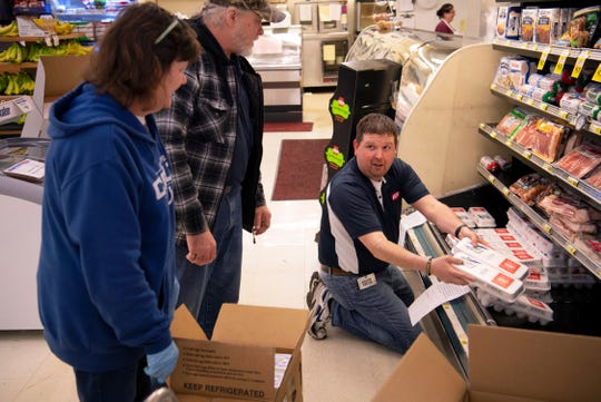 Brian Williams, right, makes room for a new shipment of eggs at the McKim's IGA in Mount Vernon, Ind., Friday morning, March 20, 2020. Food and paper products are still being delivered to the store, but there are no guarantees with the coronavirus outbreak. Toilet paper was a no-show on Friday as was fresh meat (although the store still had plenty of steak).