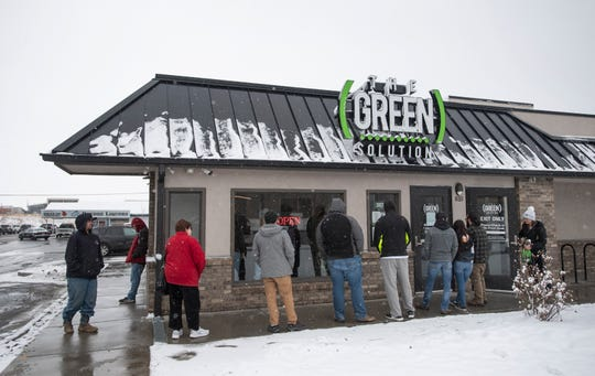 A line forms as people wait outside in the snow to enter The Green Solution Recreational Marijuana Dispensary as the community responds to the coronavirus pandemic in Fort Collins, Colo. on Friday, March 20, 2020.