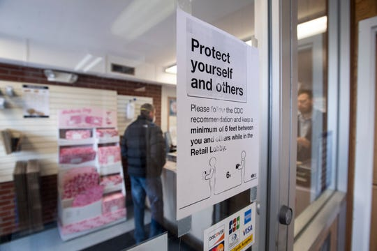 A sign advises customers to practice social distancing while waiting in the lobby at the United States Post Office on Main Street in Timnath, Colo. on Friday, March 20, 2020.