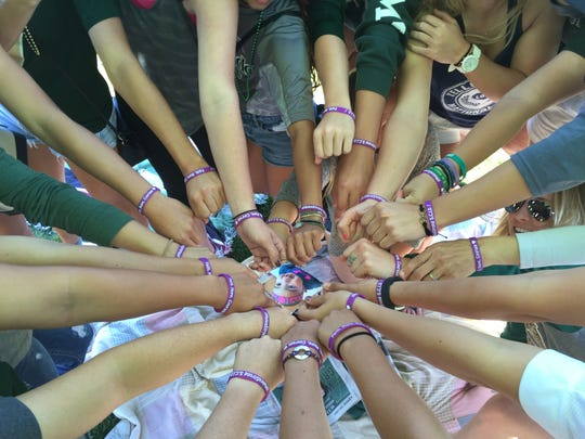 """Colorado State softball players show their support for Malea Martinez, who was born with severe combined immune disorder, with their purple """"#MaleaStrong"""" bracelets."""
