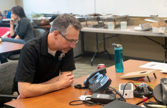 Tom Gonzales, public health director for Larimer County, speaks with officials on the phone inside the Emergency Operations Center at the Larimer County Sheriff's Office in Fort Collins, Colo. on Friday, March 20, 2020.