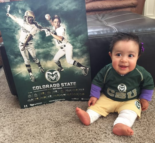 Malea Martinez sits next to a poster of the Colorado State softball team. Malea, the daughter of former assistant coach Melissa Perea-Martinez, is one of the Rams' biggest fans.