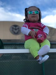 Malea Martinez sits on a fence at Colorado State softball's Ram Field. Martinez, the daughter of former assistant coach Melissa Perea-Martinez, is one of the Rams' biggest fans.