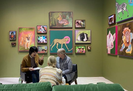 Lynn Schuster of Sturgeon Bay, right, and artist Adrian Wong of Chicago, left, meet with a pet owner at The Armory Show in New York. Schuster communicated with pets at the show so artists could create portraits of their past lives.